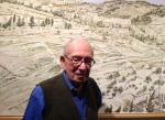 Artist Philip Pearlstein stands in front of his  panoramic view of Jerusalem, which he printed at Graphicstudio